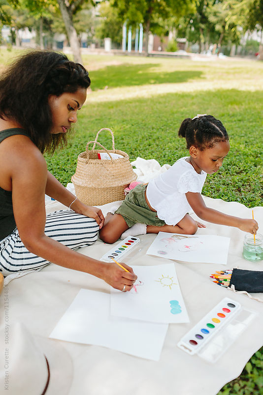 Mother and daughter painting together outdoors with paintbrushes and watercolors